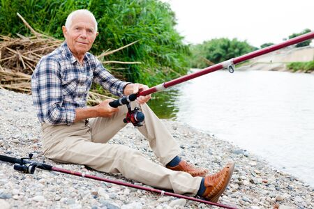 Cheerful aged man with fishing rod sitting and relaxing by lakeside