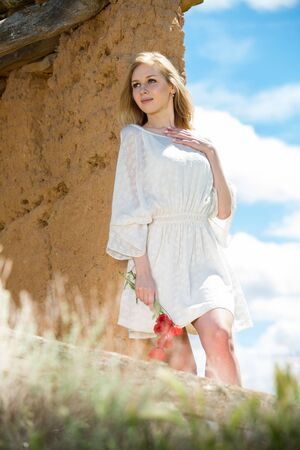 Beautiful woman wearing  white dress posing near wall  with poppies flowers  in countryside