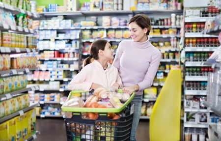 Young woman customer with girl looking for the food supplies in a supermarket. Focus on both persons