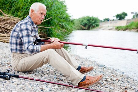Portrait of elderly man sitting and fishing at river beach at sunny day
