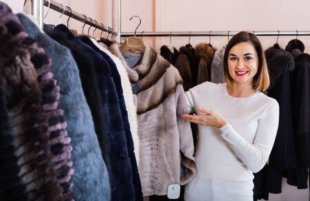 Young cheerful positive smiling woman choosing short coffee-colored fur jacket in women's cloths store 写真素材
