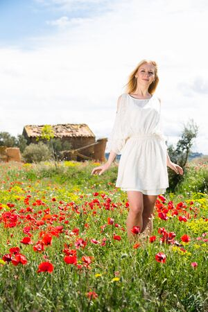 Beautiful woman wearing  white dress walking through a poppy field and enjoying summer day