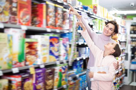 Young woman with daughter choosing breakfast cereal in supermarket