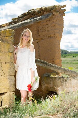 Young woman  in white dress standing near stone wall  and holding poppies plants outdoor
