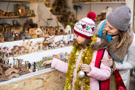 Little girl with happy mom buying figures and workpiece for creating Christmas scenes at an open air market Stok Fotoğraf