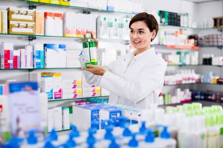 Young glad  female pharmacist suggesting useful body care products in pharmacy Banque d'images