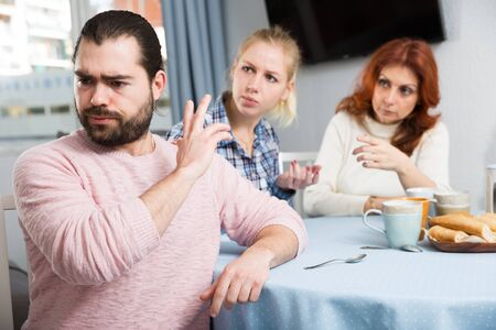 Upset young man sitting  at table after quarrel and girl with mother on background at home
