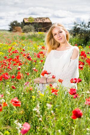 Portrait of young woman  in white dress posing  in poppies plant outdoor