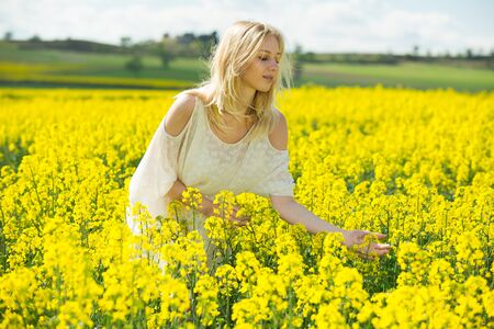 Happy girl posing  in rape seed flowers  field posing in white dress at sunny day outdoor 写真素材