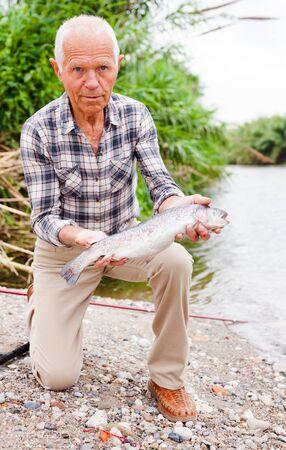 Happy adult man enjoying fishing and looking at catch fish at riverside