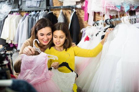 Cheerful daughter with mother are choosing comfortable dress in store.