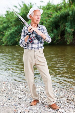 Senior man planning to fishing, standing with angling gear on riverside 스톡 콘텐츠