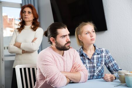 Upset mature woman talking with sad daughter and her boyfriend at home interior 写真素材