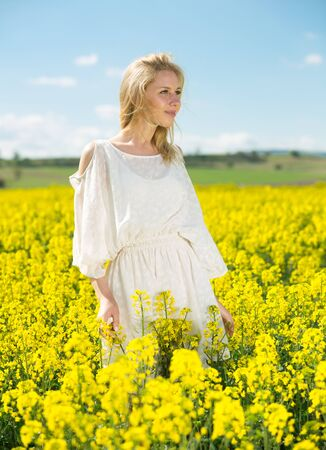 Young woman in yellow oilseed rape  field posing in white dress outdoor