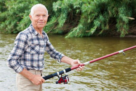 Portrait of mature man standing and fishing at river beach on summer day 스톡 콘텐츠