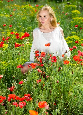Beautiful woman wearing  white dress in poppy field and enjoying summer day