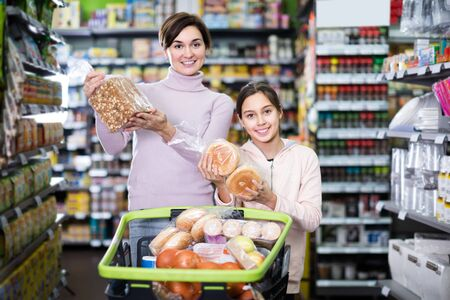 woman with daughter choosing delicious bread in supermarket