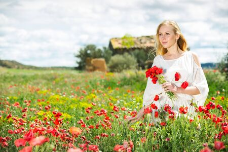 Cute woman wearing  white dress holding bouquet of  poppy  flowers  in fields at summer day
