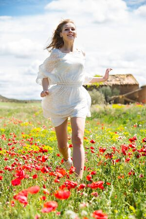 Nice woman in white dress running in field with poppies plants 写真素材