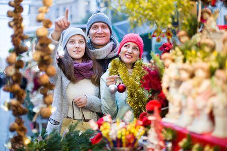 Familia feliz de tres eligiendo decoración navideña en el mercado navideño