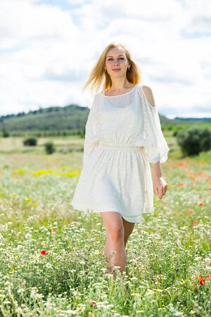 Cheerful woman wearing white dress walking  in fields with daisies flowers  outdoor