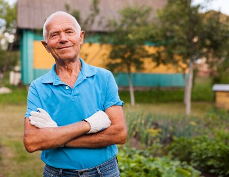 Elderly gardener posing in his garden