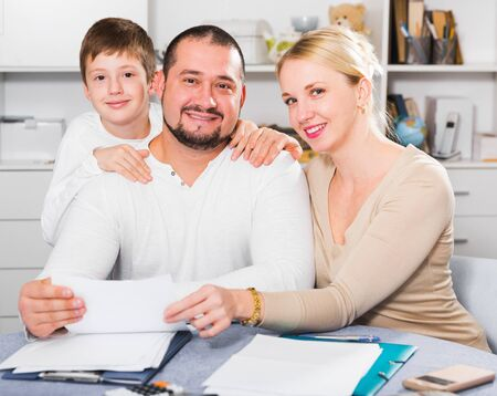 Happy friendly family of three with papers at home