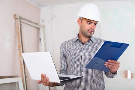 Constructor is standing with laptop and folder with documents about repair.