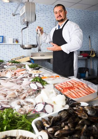 Man in black apron and white cover-slut behind counter choosing fish
