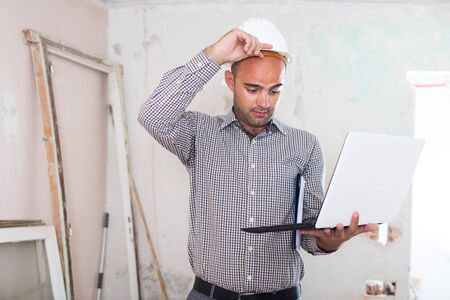 Adult man engineer surprised and working with laptop in helmet indoors