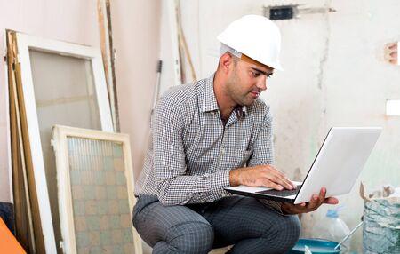 Architekt des erwachsenen Mannes, der drinnen in der Nähe des Laptops im Helm sitzt