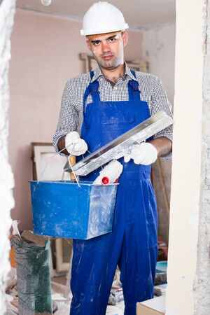Professional builder is standing with bucket and putty knife in uniform indoors.