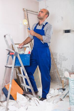 Constructor is standing with roller in uniform near the stepladder.