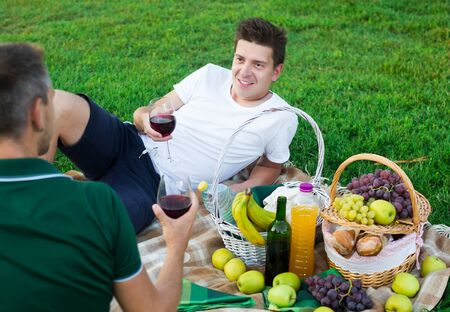 adult man with friend enjoying picnic outdoors on summer day 写真素材