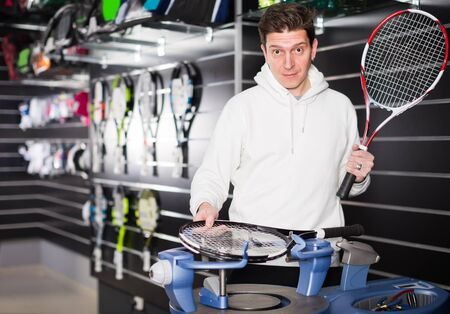 professional workman is testing the tension of new tennis rocket in the sports store