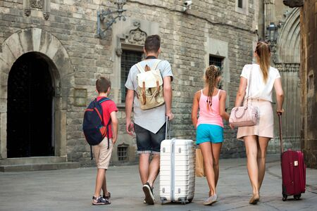 Back view of young family who are travelling together on city with baggage.