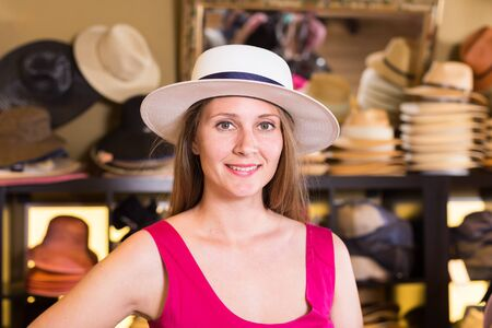 young happy american  blonde woman choose straw hat in shop