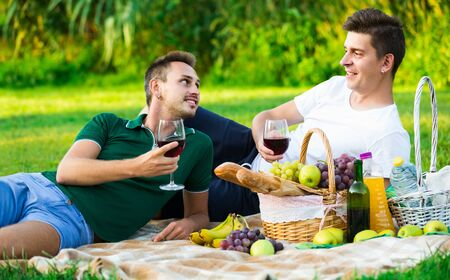 Two happy  greek males friends gaily spending time together on picnic drinking wine