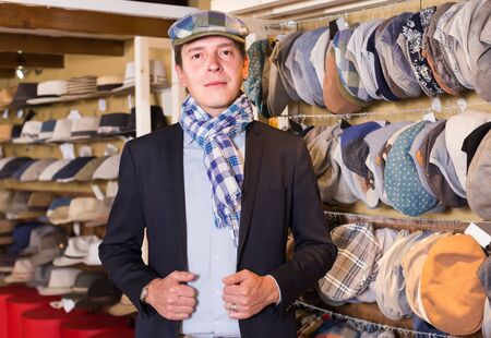portrait of positive european young male try on newboy cap at the shopping mall Reklamní fotografie