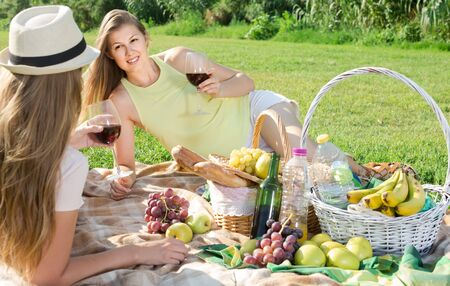 Happy european attractive woman with friend enjoying picnic outdoors on summer day