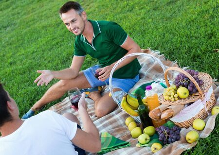 Happy  smiling man enjoying life on picnic outdoors with his friend 写真素材
