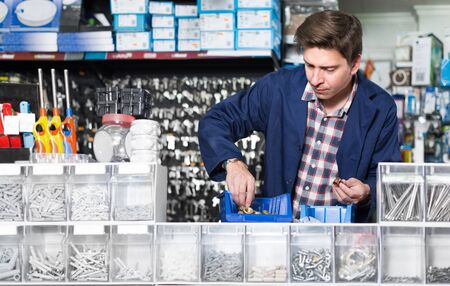 Male selling steel details for plumbing in hardware shop