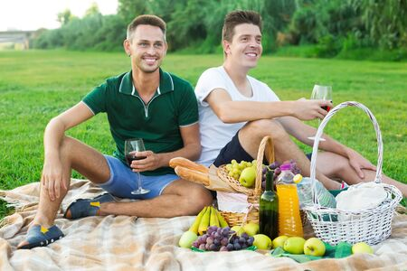 Two adult pacified  guys enjoying picnic on summer day, sitting back to back