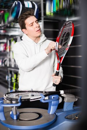 Diligent positive male master is pulling racket for tennis in the store. Stockfoto