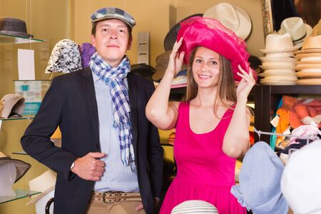 Happy woman and man trying on fashion hats in the shopping mall