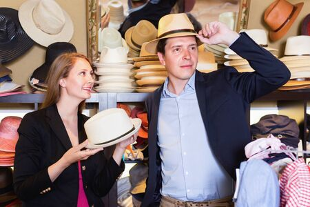 Happy cheerful girl and male try on modern hats at the boutique