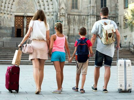Back view of family with kids who are travelling together on city with baggage.
