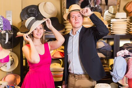 Smiling woman and man trying on fashion hats in the shopping mall Reklamní fotografie