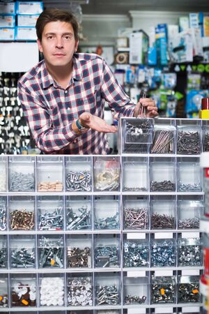 Glad employee selling nuts, screw and fasteners in hardware store