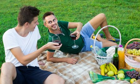 Two happy  germany males friends gaily spending time together on picnic drinking wine